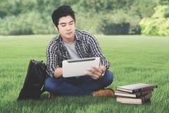 有片剂的男性大学生在草甸 库存图片