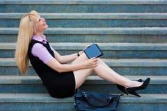 有片剂的白肤金发的女商人 库存图片