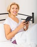 有片剂的白肤金发的成熟妇女 免版税库存图片
