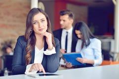 有片剂的确信的可爱的年轻女商人在手上在现代办公室开始办公室 库存照片
