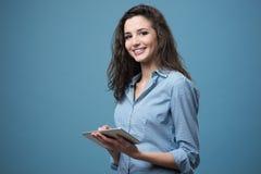 有片剂的美丽的微笑的女孩 免版税库存照片