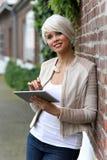 有片剂的美丽的白肤金发的妇女 免版税库存照片