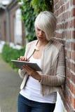 有片剂的美丽的白肤金发的妇女 免版税库存图片