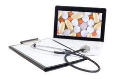 有片剂的膝上型计算机在屏幕、剪贴板和听诊器孤立 库存图片