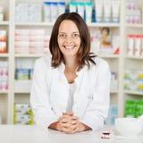 有片剂的药剂师在药房柜台 免版税图库摄影