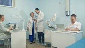 有片剂的要求年轻的人研究膝上型计算机不同的问题的医护人员 免版税库存照片