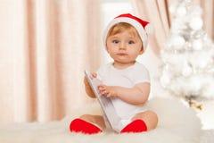 有片剂的逗人喜爱的圣诞老人婴孩 免版税库存照片