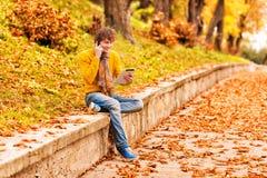 有片剂的年轻人和谈话在室外的电话 库存图片