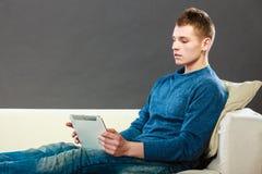 有片剂的年轻人在家坐长沙发 库存图片