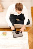 有片剂的年轻人在长沙发 免版税库存图片