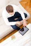 有片剂的年轻人在长沙发 库存照片