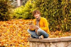 有片剂的年轻人室外秋天 免版税图库摄影