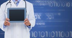 有片剂的医生反对白色二进制编码和蓝色背景 库存图片