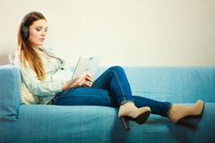 有片剂耳机的妇女坐长沙发 免版税图库摄影