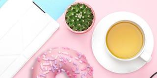 有片剂计算机、甜多福饼、仙人掌、茶杯子在桃红色和蓝色淡色背景的平的被放置的办公室桌书桌 ?? 免版税库存照片