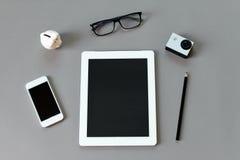 有片剂计算机、铅笔、眼睛玻璃、小行动照相机、存钱罐和巧妙的电话的工作区书桌在灰色背景 免版税库存图片