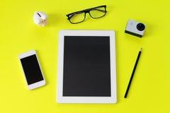 有片剂计算机、铅笔、眼睛玻璃、小行动照相机、存钱罐和巧妙的电话的工作区书桌在黄色背景 库存图片