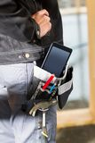 有片剂计算机和工具的木匠在站点的袋子 免版税图库摄影