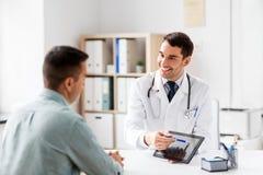 有片剂计算机和患者的医生诊所的 免版税库存照片
