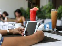 有片剂计算机和水果饮料的妇女手 免版税库存图片
