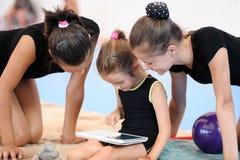 有片剂计算机的三个体操运动员女孩 库存照片