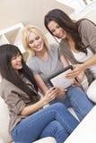 有片剂计算机的三个美丽的妇女朋友 免版税图库摄影