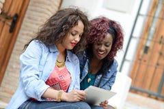 有片剂计算机的两个美丽的女孩在都市backgrund 库存照片