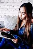 有片剂计算机的可爱的女孩在她的手上 库存图片