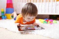 有片剂计算机的可爱的小男孩在家 免版税库存图片