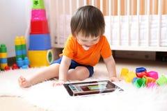 有片剂计算机的可爱的婴孩在家 库存照片