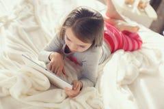 有片剂计算机的小女孩在床上 库存图片