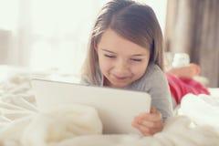 有片剂计算机的小女孩在床上 免版税库存照片