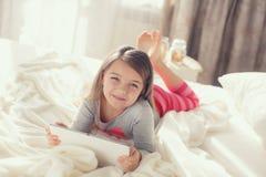 有片剂计算机的小女孩在床上 免版税库存图片