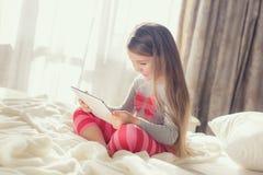 有片剂计算机的小女孩在床上 库存照片