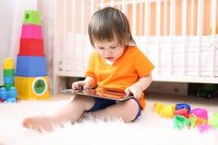有片剂计算机的小男孩在家 图库摄影