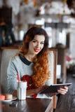 有片剂计算机的少妇在咖啡馆 免版税库存照片