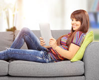 有片剂计算机的少妇在沙发在家 免版税库存图片