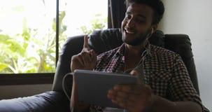 有片剂计算机的年轻人听在家坐在扶手椅子的o音乐,混合种族人佩带的耳机唱歌 影视素材
