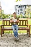 有片剂计算机的微笑的偶然人坐长凳 免版税库存图片