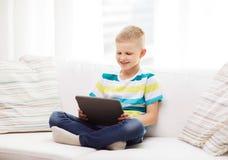 有片剂计算机的微笑的男孩在家 库存照片