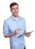 有片剂计算机的愉快的澳大利亚人 免版税库存照片