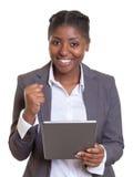 有片剂计算机的愉快的非洲女实业家 图库摄影
