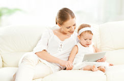 有片剂计算机的母亲和小孩子在长沙发在家 库存图片