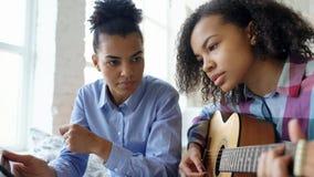有片剂计算机的混合的族种少妇坐床教她的少年姐妹的在家弹声学吉他 免版税图库摄影