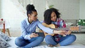 有片剂计算机的混合的族种少妇坐床教她的少年姐妹的在家弹声学吉他 免版税库存照片