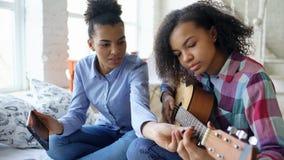 有片剂计算机的混合的族种少妇坐床教她的少年姐妹的在家弹声学吉他 免版税库存图片
