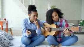 有片剂计算机的混合的族种少妇坐床教她的少年姐妹的在家弹声学吉他 图库摄影
