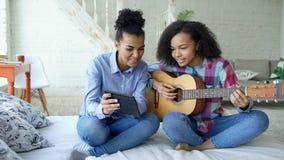 有片剂计算机的混合的族种少妇坐床教她的少年姐妹的在家弹声学吉他 库存照片