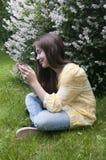 有片剂计算机的美丽的少年女孩坐草在公园 照片 库存照片