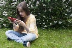 有片剂计算机的美丽的少年女孩坐草在公园 照片 图库摄影